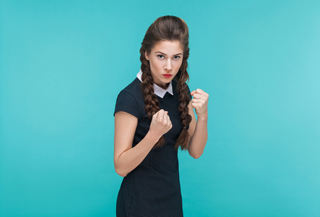 Boxing concept. Aggressive woman looking at camera with dangerous look. Indoor, studio shot on blue background